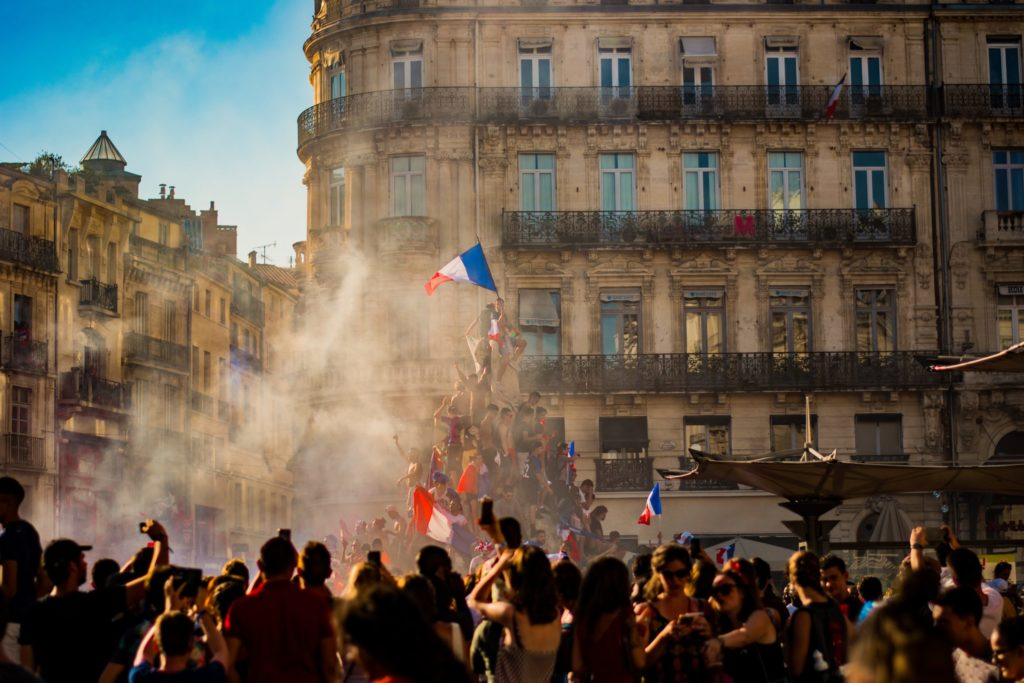people waving flag of France near building